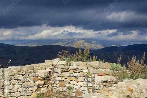 Aluminium Beige Landschaft mit dunkeln Wolken und Steinmauer