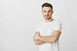 Intrigued smart young male entrepreneur in white t-shirt with moustache smirking holding hands crossed on chest feeling satisfied and glad receiving great result in sales over gray background