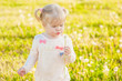Funny baby girl blowing a dandelion - 216508103
