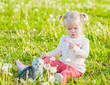 Baby girl with kitten blowing dandelion on green summer grass