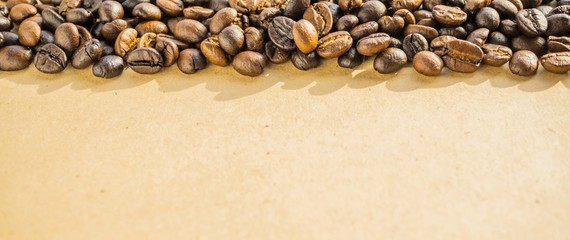 macro of coffee beans on rustic paper background © mvdesign