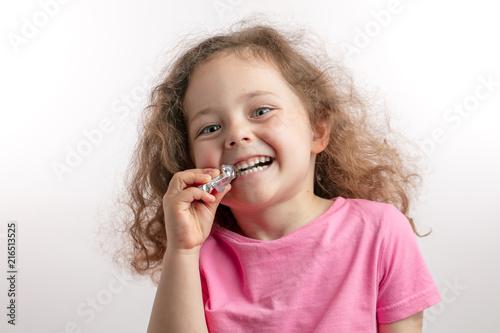 Leinwandbild Motiv little smiling girl likes chocolate. isolated white background. copy space.