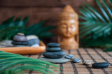 Pyramids of gray zen stones with green leaves and Buddha statue. Concept of harmony, balance and meditation, spa, massage, relax