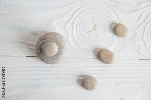 Plexiglas Zen Pyramids of white zen stones with green leaves on white background. Concept of harmony, balance and meditation, spa, massage, relax