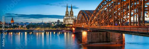 Leinwanddruck Bild Skyline von Köln mit Kölner Dom und Hohenzollernbrücke bei Nacht