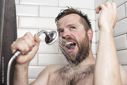 Fototapeta Cute bearded man singing in the bathroom using the shower head with flowing water instead of a microphone.