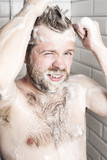 Attractive bearded man washing her hair in the shower under running water.