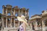 Blonde woman with hat looking at Celsus library in Ephesus, Izmir, Turkey