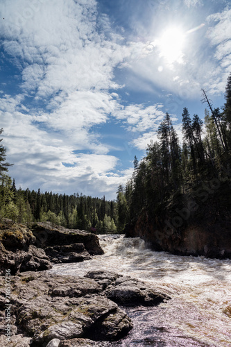 Foto Spatwand Bergrivier River in Finland Lappland with some blue sky and trees
