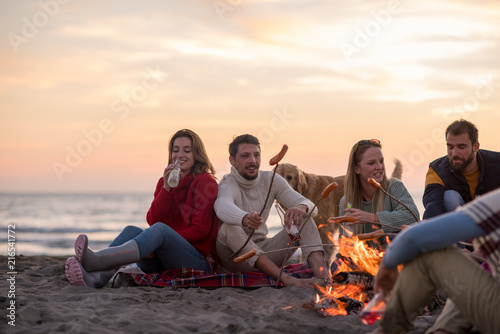 Leinwanddruck Bild Group Of Young Friends Sitting By The Fire at beach