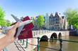 Plane travel concept, hand holding passports with plane over Amsterdam background