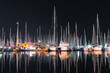 Leinwandbild Motiv Many yachts sail boats in marina bay at night mirroring in a sea