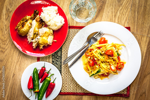 A traditional Thai meal of  papaya salad (som tam) with roast chicken, sticky rice, chillies and water - 216550354