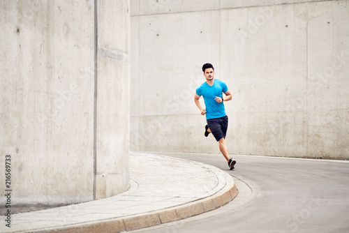 Foto Spatwand Hardlopen Athletic man running on road in the city. Outdoors training concept