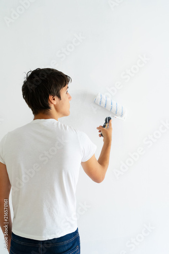 Young men painting wall of her house in white, do it yourself home