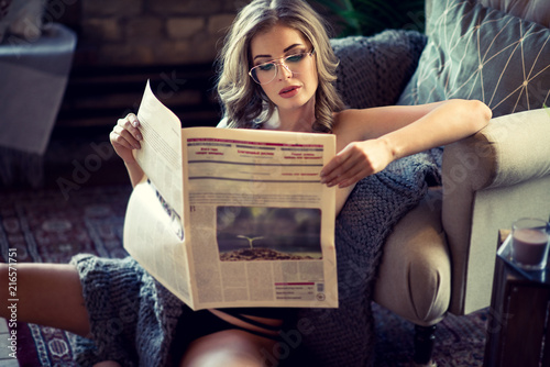 Leinwanddruck Bild Female portrait of cute lady with newspaper indoors