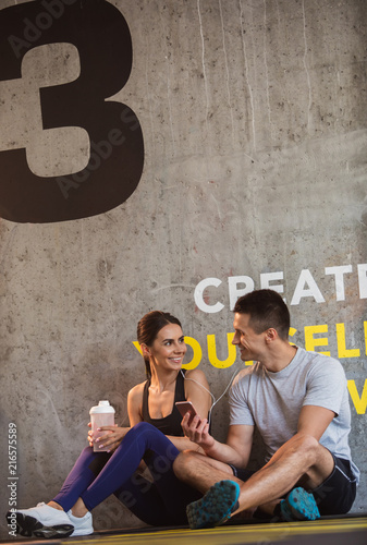 Leinwandbild Motiv Cheerful couple is relaxing during break in workout in gym. They are sitting on floor and sharing earphones while enjoying audios. Man is holding smartphone while girl is drinking water from sport