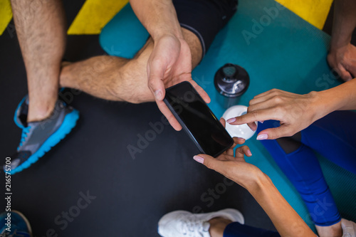 Leinwandbild Motiv Top view close up of smartphone held both by male and female hands. Two sportspeople are sitting on mats in sport studio with bottles of water. Woman is pointing at screen for attracting man attention