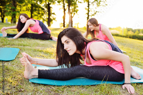 Wall mural group of people doing yoga on the green with fresh grass outdoors. Healthy lifestyle