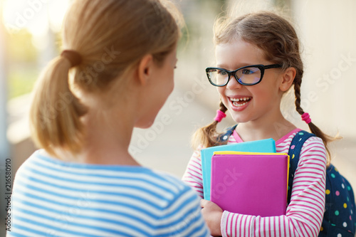 first day at school. mother leads  little child school girl in first grade. - 216580910