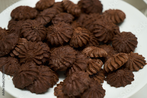 Foto Murales Cookies and sweet biscuits on white plate background, top view