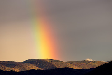 Beautiful and surreal view of part of a rainbow over some hills