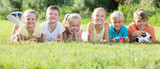 Group of friendly kids lying on green grass in park - 216607794