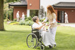 Friendly caregiver giving tea to paralysed elderly woman in the wheelchair on green grass