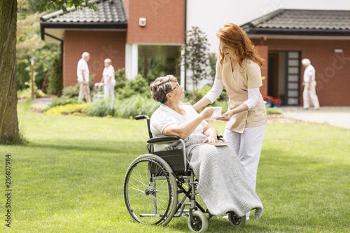 Leinwanddruck Bild Friendly caregiver giving tea to paralysed elderly woman in the wheelchair on green grass