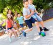 Leinwandbild Motiv Happy children  playfully running after ball outdoors in park