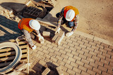 High angle of workers in white helmets arranging a paving stone - 216610176