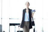 Cheerful and successful businesswoman with luggage moving inside modern airport after arrival - 216610709