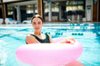 canvas print picture - Young restful female in pink pool buoy looking at camera while swimming by hotel at spa resort