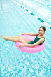 canvas print picture - Joyful young woman sitting inside pink pool buoy and enjoying summer day in water