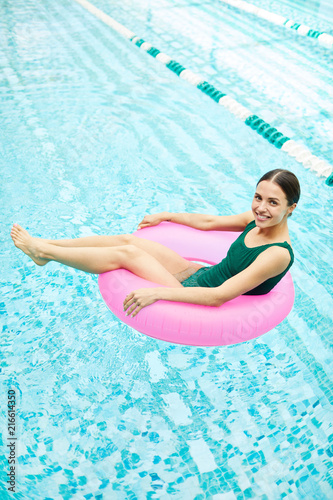 canvas print picture Joyful young woman sitting inside pink pool buoy and enjoying summer day in water
