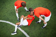Leinwandbild Motiv Two young football players in uniform leaning over their mate lying on field with hurt knee
