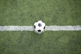 Overview of leather ball for playing soccer in the middle of dividing line on green field