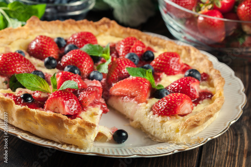 Leinwanddruck Bild Tart with curd cheese, strawberries and blueberries