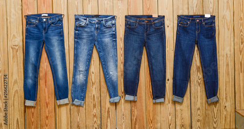 Leinwandbild Motiv Four blue Jeans- wooden background