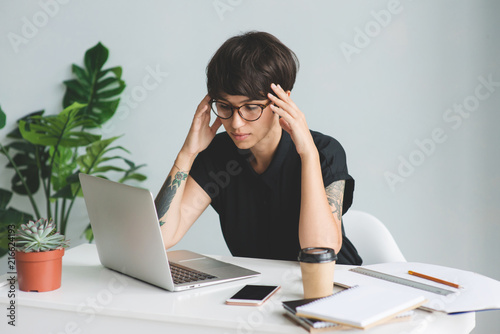 Leinwanddruck Bild Tired businesswoman in glasses at workplace in office.