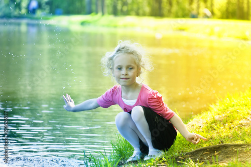 Leinwanddruck Bild young blonde girl in summer at the lake