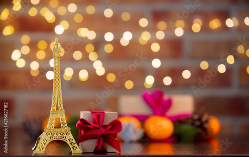 golden eiffel tower souvenir on background with fairy lights in bokeh. Christmas Holiday season