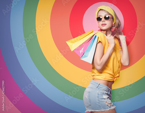 Foto Murales Young redhead girl in yellow t-shirt and blue jeans holding a colorful bags on pink background