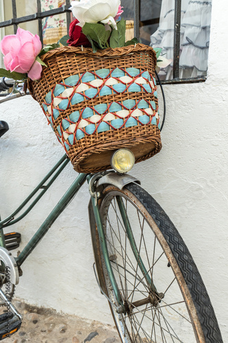 Foto Spatwand Fiets Vintage bicycle parked with basket of beautiful flowers. Old bike on the street leaning on the perimeter with window