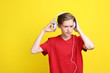 Cute teenager with headphones on yellow background