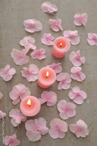 Plexiglas Spa Pink hydrangea petals with three candle on gray background