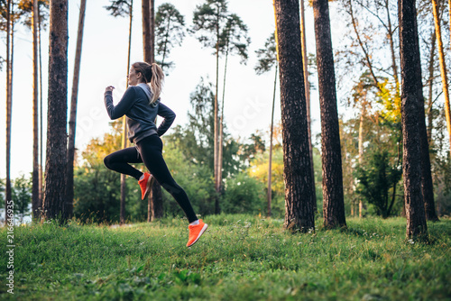 Foto Spatwand Hardlopen Young female athlete jogging in forest. Jogger doing morning physical training.