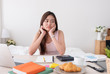 Asian woman freelancer rest chin on hand with bore feeling with work problem with laptop on mess table.work at home concept.stress working. - 216649540
