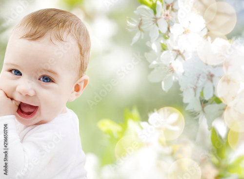 Foto Murales childhood and people concept - close up of sweet little baby  over cherry blossom background