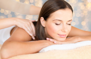 wellness, spa and beauty concept - close up of beautiful woman having massage over holidays lights background